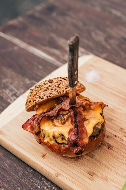 木の板においしいベーコンチーズバーガー。 Premium写真