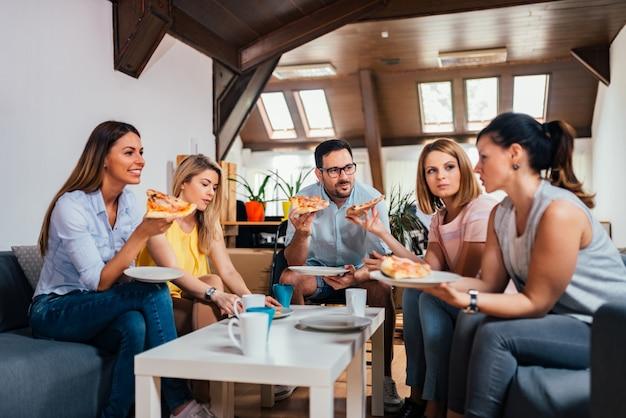 Друг разговаривает и ест пиццу в домашних условиях. Premium Фотографии