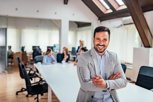 Красивый исполнительный, улыбаясь в офисе Premium Фотографии