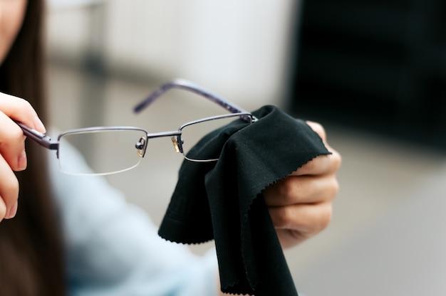 黒い布で彼女のメガネを掃除する女性。 Premium写真
