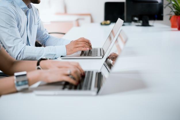 オフィスで働く日。ビジネスマンの手がオフィスのノートパソコンのキーボードで入力します。 Premium写真