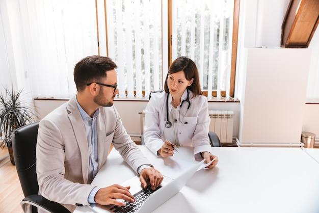 Бизнесмен разговаривает с женщина-врач в больнице Premium Фотографии