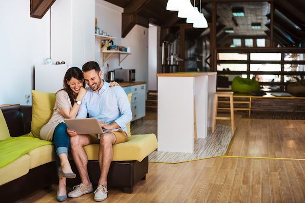 Молодая пара вместе отдохнуть на большой удобный диван с ноутбуком в интернете. Premium Фотографии