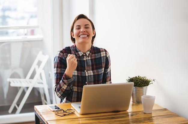 良いニュースを読んで興奮しているカジュアルな起業家の女の子 Premium写真
