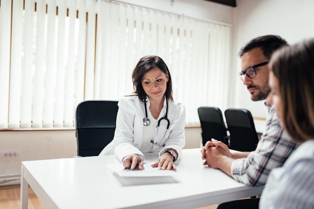 医者は診療所でカップルと議論します。 Premium写真