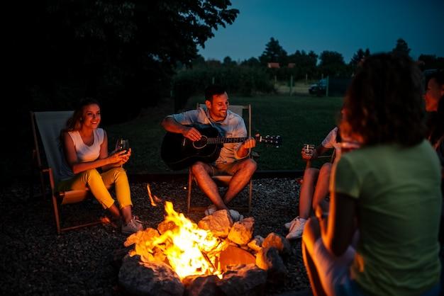Группа друзей, наслаждаясь музыкой вокруг костра ночью. Premium Фотографии