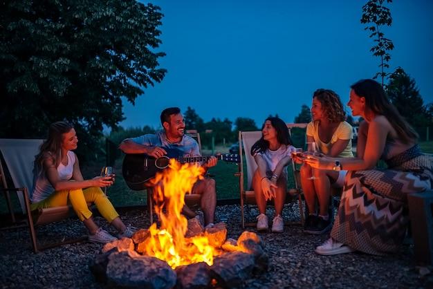 友達が音楽を演奏し、自然の中でたき火を楽しんでいます。 Premium写真