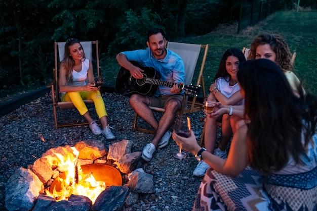 キャンプファイヤーの周りに楽しい時間を過ごしている友人のグループ。 Premium写真