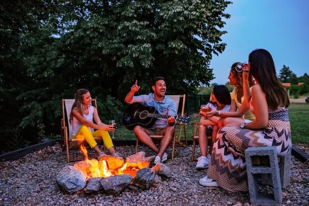 キャンプファイヤーの周り楽しんでいる友人のグループ。ギターを弾く、歌う、飲む。 Premium写真