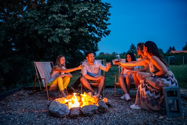 Друзья поджаривают, сидя у костра. Premium Фотографии