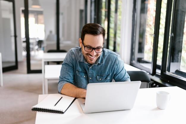 明るいオフィススペースでラップトップを使用して朗らかビジネスマン。 Premium写真