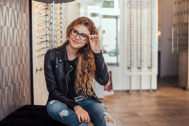 光学店で新しいメガネと美しい女性。 Premium写真