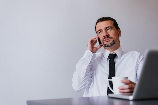 Красивый зрелый бизнесмен разговаривает по мобильному телефону. Premium Фотографии