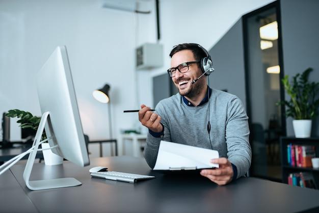 ヘルプデスクで働いてハンサムな笑みを浮かべて男。 Premium写真
