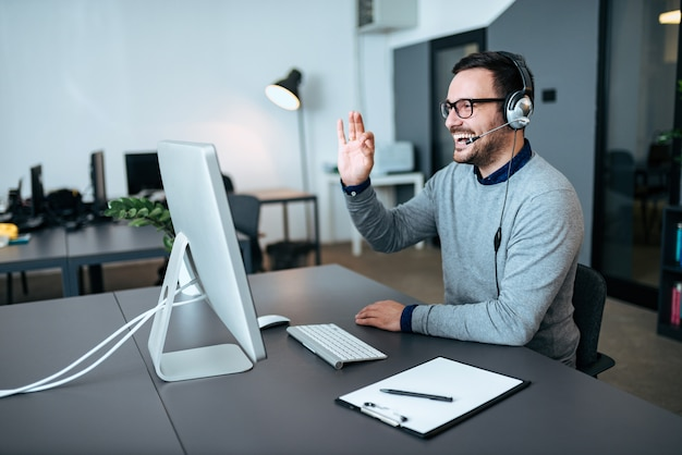 ハンサムなテクニカルサポート担当者がクライアントと話して、彼に大丈夫なサインを与えます。ビデオ通話。 Premium写真