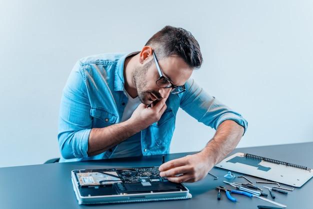 ラップトップコンピューターを修復しながら携帯電話で話しているハンサムなコンピューターエンジニア。 Premium写真