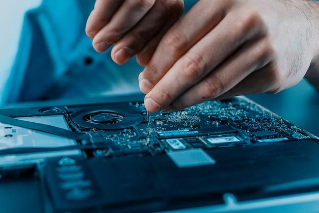 ノートパソコンを修理する男性の手のクローズアップ。ハードウェア Premium写真
