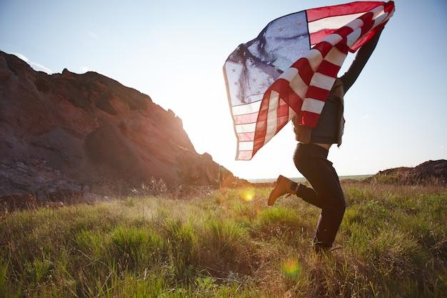 アメリカの国旗を実行しているうれしそうな男 無料写真
