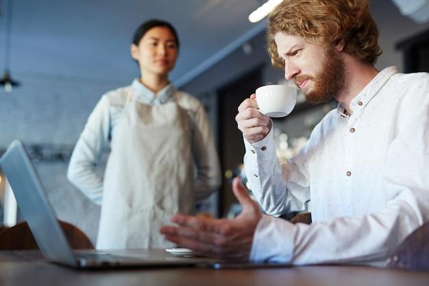 ノートパソコンで作業しながらコーヒーやお茶を飲む男性 無料写真