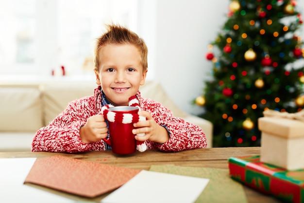 クリスマスに飲み物を持つ少年 無料写真