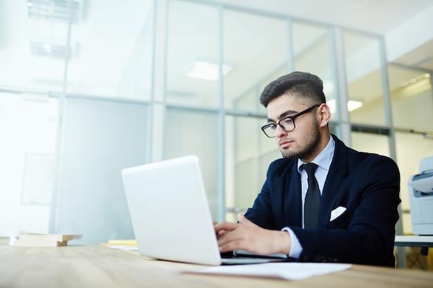 オフィスでラップトップで働くビジネスマン 無料写真