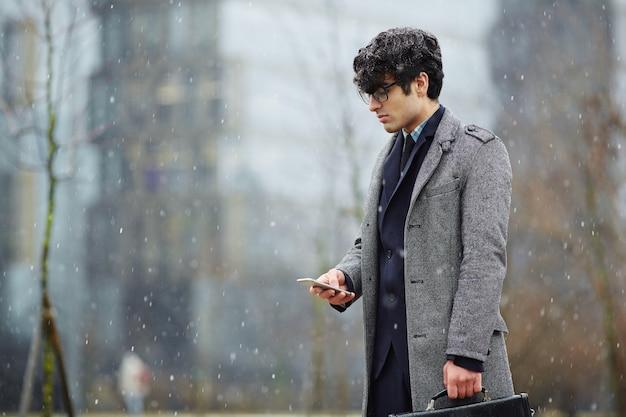 Бизнесмен с помощью смартфона на снежной улице Бесплатные Фотографии