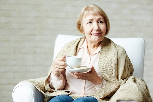 お茶を楽しむ高齢者の女性 無料写真