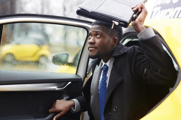雨の中でタクシーを残してアフリカの実業家 無料写真