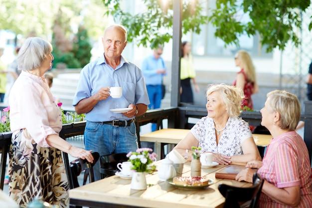 屋外カフェで時間を過ごす高齢者 無料写真