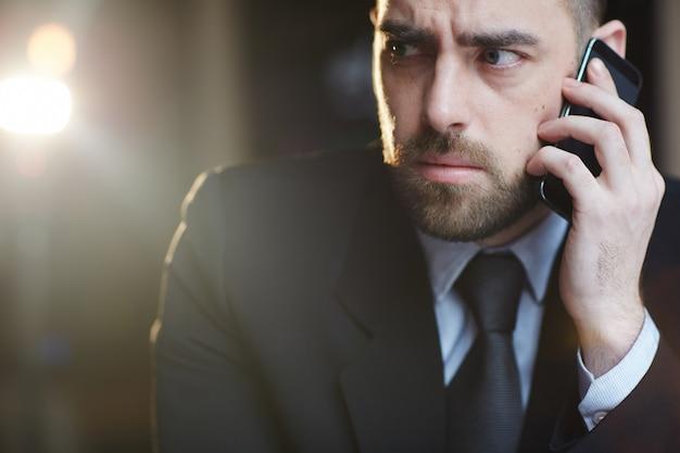 Смущенный бизнесмен, говорящий по смартфону Бесплатные Фотографии