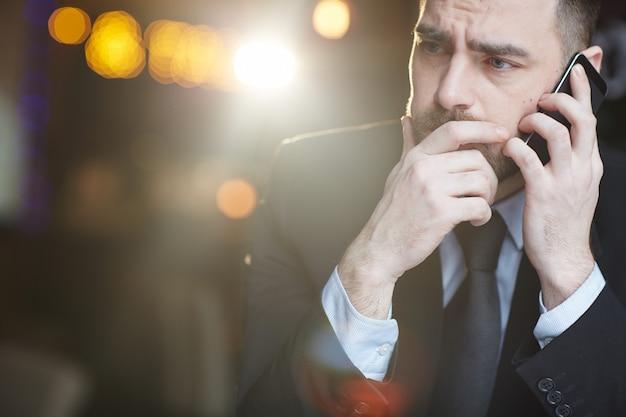 スマートフォンで話している渋面の実業家 無料写真
