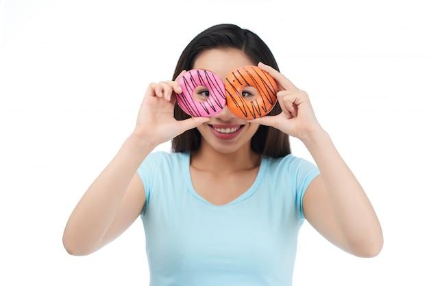 食欲をそそるドーナツとうれしそうなアジアの女性 無料写真