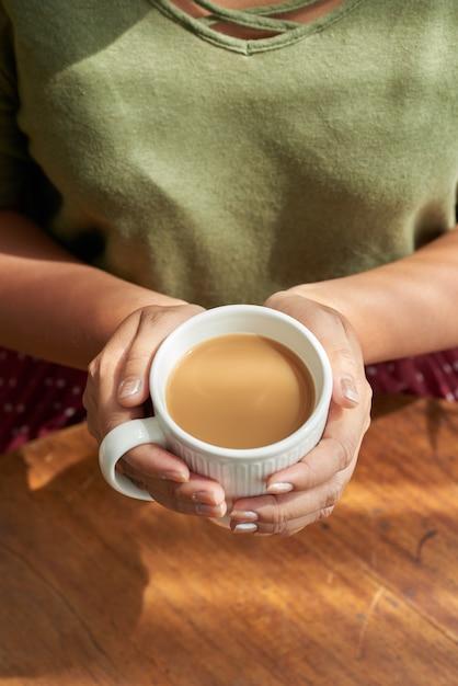 Женщина держит чашку капучино Бесплатные Фотографии
