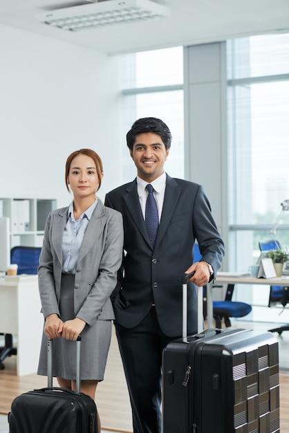 出張前にスーツケースとオフィスでポーズをとってスーツを着た男女の膝のショット 無料写真