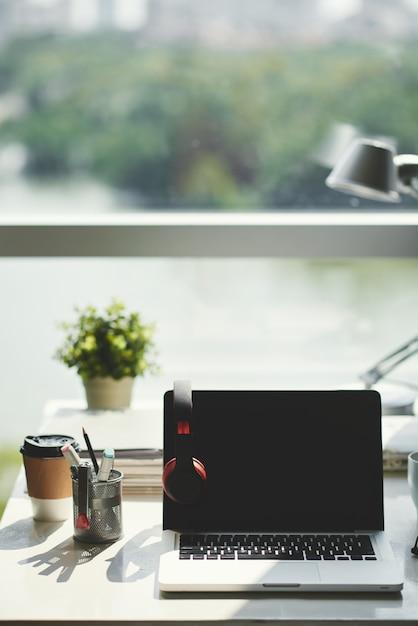 Снимок объекта выключенного ноутбука с открытой крышкой, черным экраном и наушниками, на столе в офисе перед окном в дневное время Бесплатные Фотографии