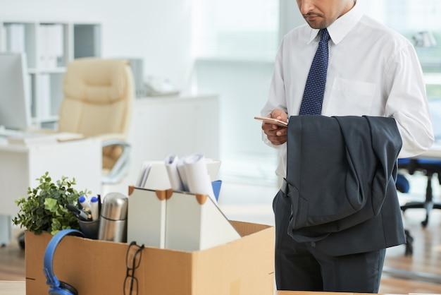 認識できない男のオフィスに立っていると、ボックス内の私物で、スマートフォンを使用して 無料写真