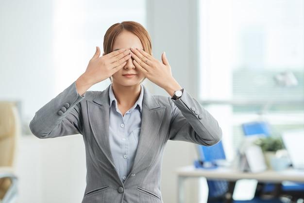 Женщина в деловом костюме стоит в офисе с руками, охватывающими глаза Бесплатные Фотографии