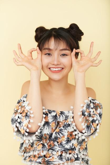 若い中国人女性が面白い手ジェスチャーでスタジオでポーズ 無料写真