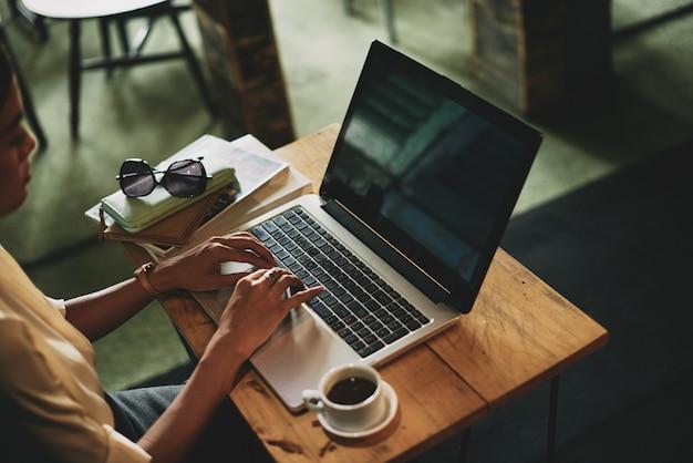 カフェに座っているとラップトップに取り組んで認識できないアジアの女性 無料写真