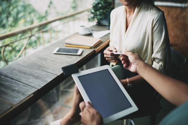 カフェで女性からクレジットカードを受け入れるタブレットで認識できないウェイターのハイアングルショット 無料写真