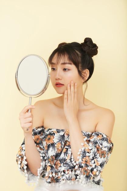スタジオでポーズをとって手に鏡を見て裸の肩を持つ若いアジア女性 無料写真