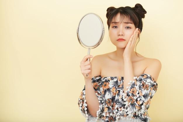 若いアジア女性の手鏡を保持していると不幸な顔でカメラ目線 無料写真