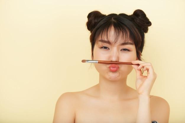 彼女の唇と鼻の間のアイシャドウブラシで顔をゆがめた若いアジア女性 無料写真