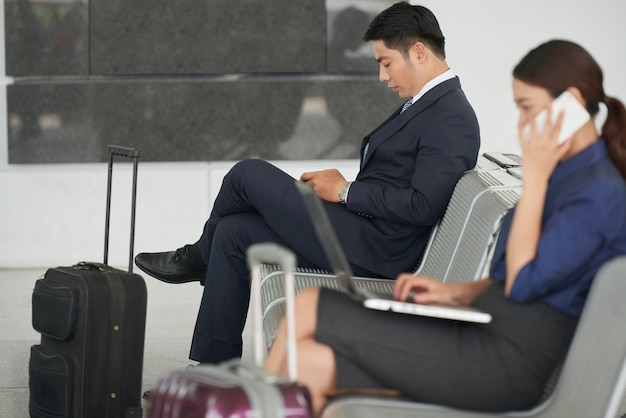 Красивый азиатский бизнесмен ждет в аэропорту Бесплатные Фотографии