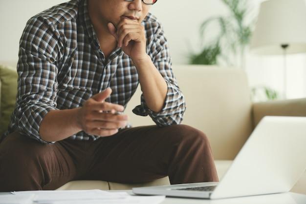 自宅のソファに座ってノートパソコンの画面を見ている男 無料写真