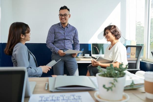 Трое коллег обсуждают проект на приеме в офисе Бесплатные Фотографии