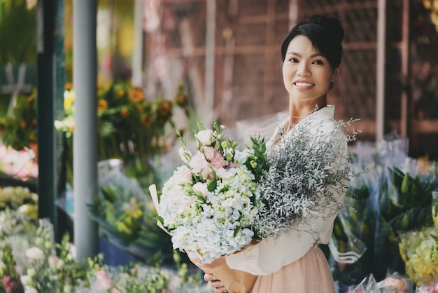 大きな精巧な花束とフラワーショップに近いポーズ身なりのアジア女性 無料写真