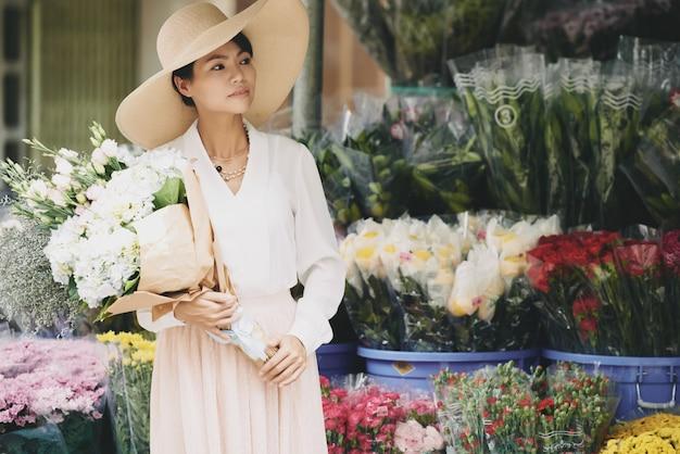 フラワーショップの外で待っている大きな花束とエレガントな裕福なアジアの女性 無料写真