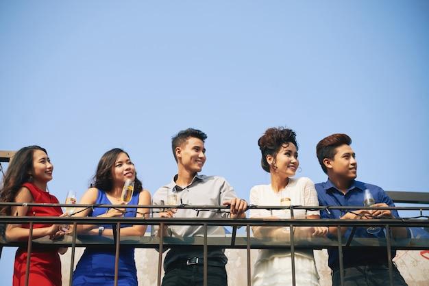 手すりに寄りかかって目をそらして華やかなアジアパーティーのゲストのグループ 無料写真