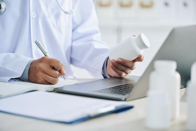 До неузнаваемости женщина-врач с ноутбуком держит лекарства и пишет рецепт Бесплатные Фотографии